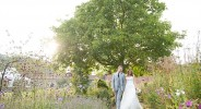 bride and groom hand in hand in an english garden at sunset