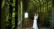 bride and groom portrait in garden covered walkway hampton court palace gardens