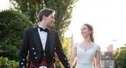 groom in kilt walking hand in hand with bride at sunset in london