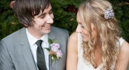bride with loose curled hair sits close to groom with grey three piece suit in garden